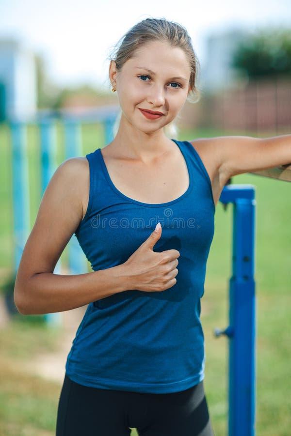 Το όμορφο νέο κορίτσι σε ένα μπλε πουκάμισο και τις περικνημίδες στον υπαίθριο χώρο αθλήσεων το καλοκαίρι παρουσιάζει αντίχειρα,  στοκ εικόνες με δικαίωμα ελεύθερης χρήσης
