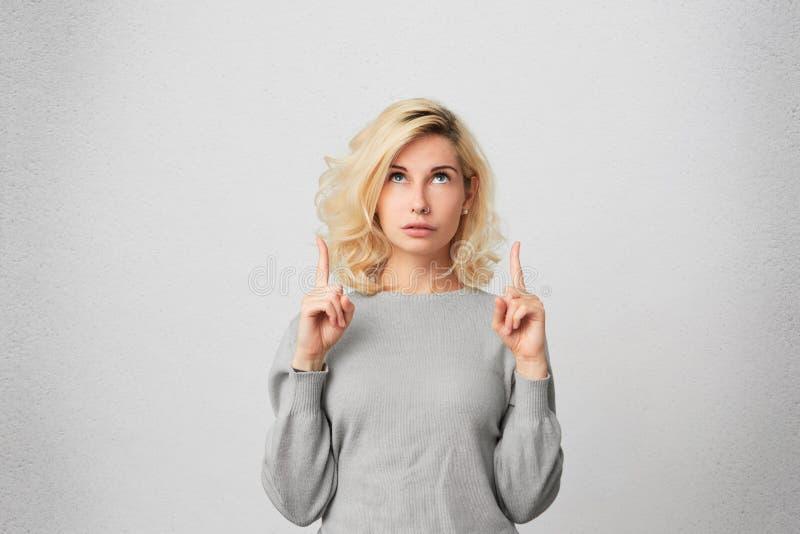 Το όμορφο ξανθό θηλυκό με τη διαπερασμένη μύτη, φορά το γκρίζο πουλόβερ κοιτάζει στο amazement όπως δείχνει σε κάτι προς τα πάνω στοκ εικόνα