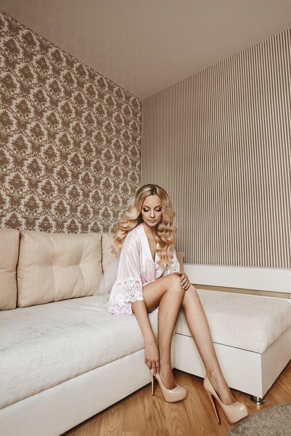 Το όμορφο ξανθό πρότυπο κορίτσι με τα μακροχρόνια προκλητικά πόδια κα στοκ φωτογραφίες