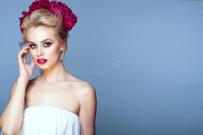 Το όμορφο ξανθό πρότυπο με την τρίχα updo και τέλειος αποτελεί τη φθορά της peony επικεφαλής γιρλάντας σχετικά με το πρόσωπό της στοκ φωτογραφίες