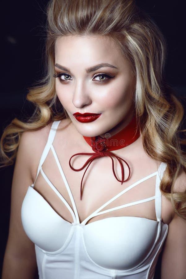 Το όμορφο ξανθό πρότυπο χαμόγελου με τέλειο αποτελεί και απέρριψε την πίσω τρίχα που φορά τον άσπρο κορσέ δεμένο τοπ και κόκκινο  στοκ εικόνες