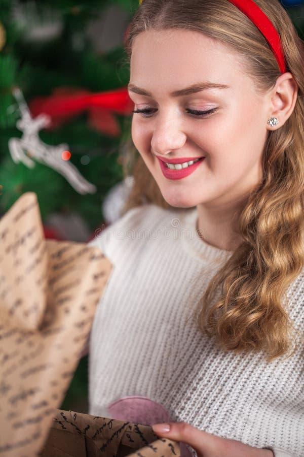 Το όμορφο ξανθό firl ανοίγει ένα νέο δώρο έτους ` s στο backg στοκ φωτογραφία με δικαίωμα ελεύθερης χρήσης