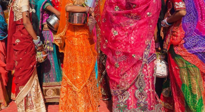 Το όμορφο πλήθος των γυναικών colorfu έντυσε την παραδοσιακή ινδική Sari με τα σχέδια που πηγαίνουν για το νερό με τα βάζα στοκ φωτογραφία
