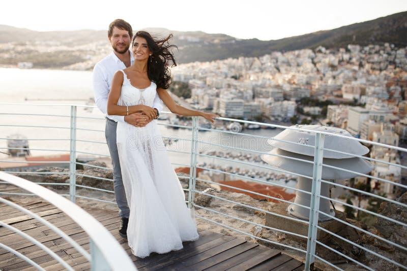Το όμορφο πορτρέτο ενός ακριβώς παντρεμένου νέου ζευγαριού, θέτει να αγκαλιάσει πίσω μιας παλαιών πόλης και ενός θαλάσσιου λιμένα στοκ φωτογραφία