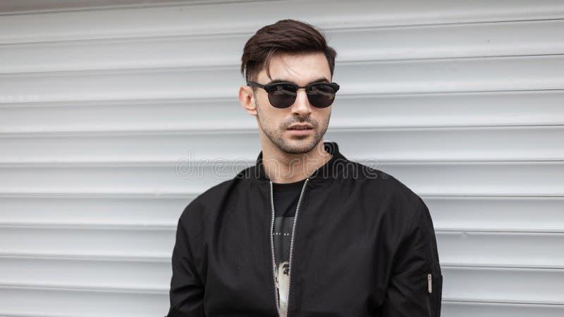Το όμορφο προκλητικό νέο άτομο hipster στα καθιερώνοντα τη μόδα γυαλιά ηλίου σε ένα μαύρο σακάκι με ένα μοντέρνο hairstyle θέτει  στοκ εικόνα