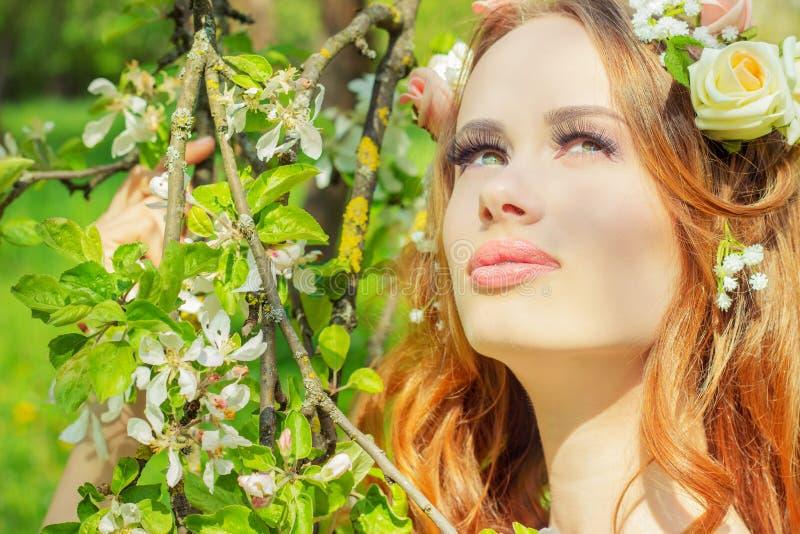 Το όμορφο προκλητικό κορίτσι με την κόκκινη τρίχα με τα λουλούδια στην τρίχα της στέκεται κοντά τα ανθίζοντας δέντρα της Apple στοκ φωτογραφία με δικαίωμα ελεύθερης χρήσης