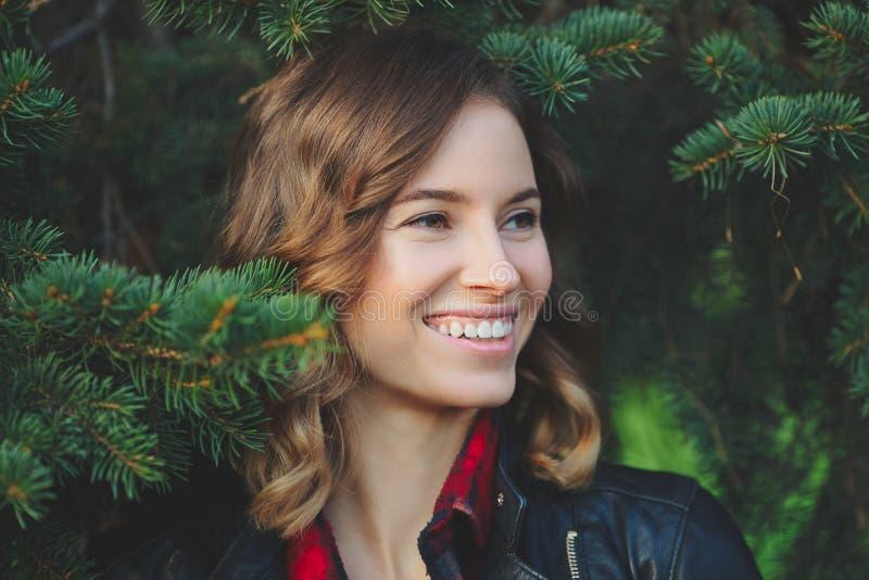 Το όμορφο πρόσωπο μιας χαμογελώντας νέας γυναίκας σε ένα κλίμα του έλατου διακλαδίζεται στοκ φωτογραφία με δικαίωμα ελεύθερης χρήσης