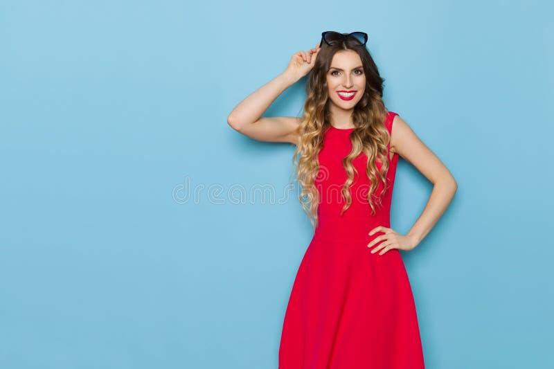 Το όμορφο πρότυπο μόδας στο κόκκινο φόρεμα χαμογελά και εξετάζει τη κάμερα στοκ εικόνα με δικαίωμα ελεύθερης χρήσης