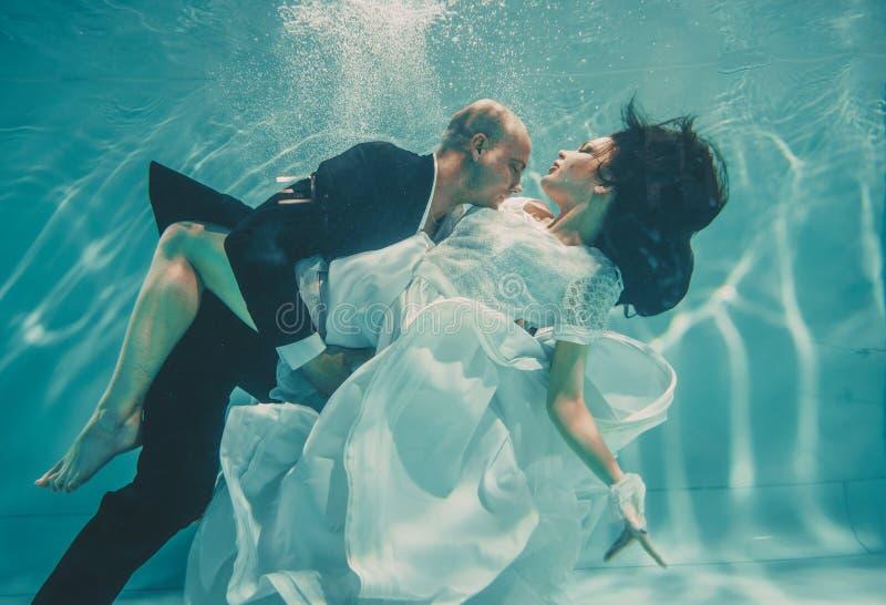 Το όμορφο ρομαντικό ζεύγος της νύφης και ο νεόνυμφος μετά από το γάμο που κολυμπούν ήπια κάτω από το νερό και χαλαρώνουν στοκ εικόνες