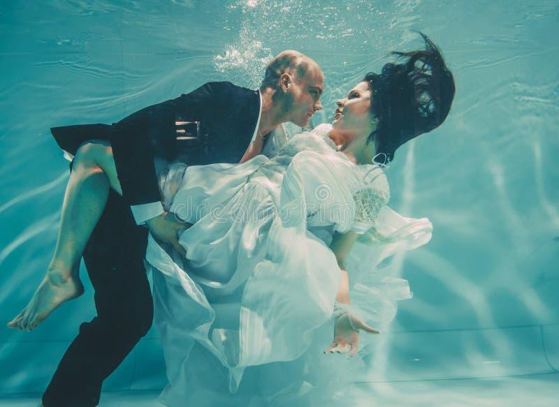 Το όμορφο ρομαντικό ζεύγος της νύφης και ο νεόνυμφος μετά από το γάμο που κολυμπούν ήπια κάτω από το νερό και χαλαρώνουν στοκ εικόνα