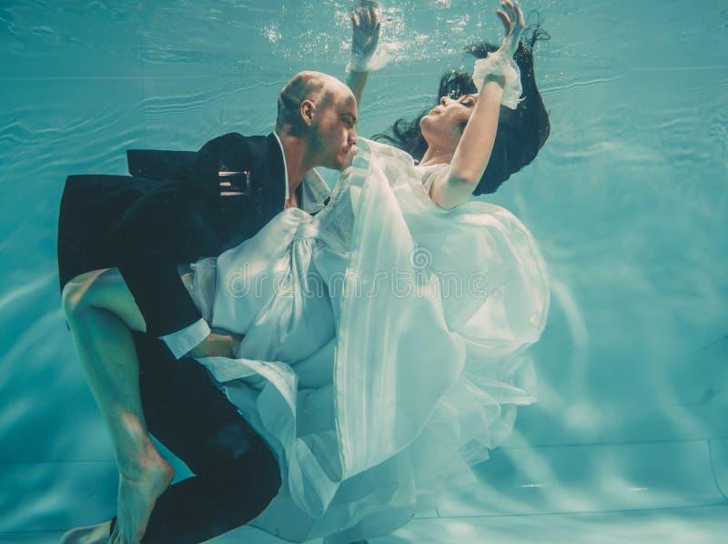 Το όμορφο ρομαντικό ζεύγος της νύφης και ο νεόνυμφος μετά από το γάμο που κολυμπούν ήπια κάτω από το νερό και χαλαρώνουν στοκ φωτογραφίες