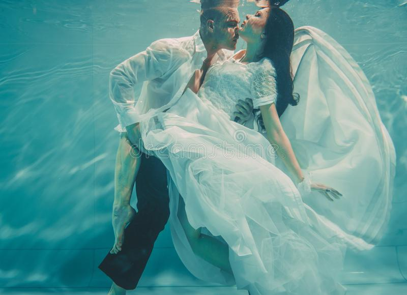 Το όμορφο ρομαντικό ζεύγος της νύφης και ο νεόνυμφος μετά από το γάμο που κολυμπούν ήπια κάτω από το νερό και χαλαρώνουν στοκ εικόνα με δικαίωμα ελεύθερης χρήσης
