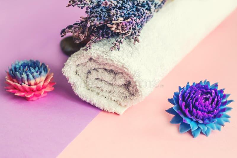 Το όμορφο σαπούνι υπό μορφή λουλουδιών και πετσέτας με lavender ανθίζει για τις επεξεργασίες SPA σε ένα δίχρωμο υπόβαθρο Εκλεκτικ στοκ φωτογραφία με δικαίωμα ελεύθερης χρήσης