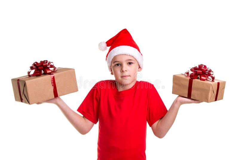 Το όμορφο σοβαρό αγόρι, καπέλο santa στο κεφάλι του, με δύο κιβώτια δώρων σε ετοιμότητα, που μπερδεύονται για να κάνουν το α μετα στοκ εικόνες
