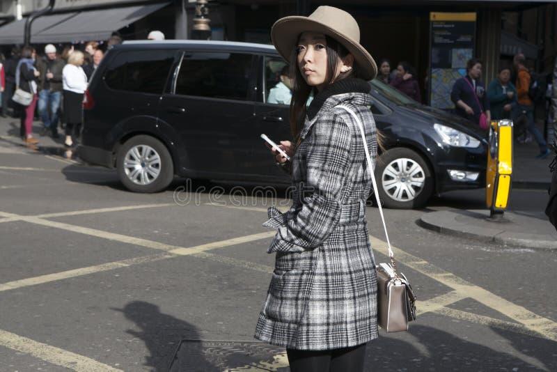 Το όμορφο σοβαρό ασιατικό κορίτσι σε ένα μπεζ καπέλο και ένα καρό ντύνουν cro στοκ φωτογραφία με δικαίωμα ελεύθερης χρήσης