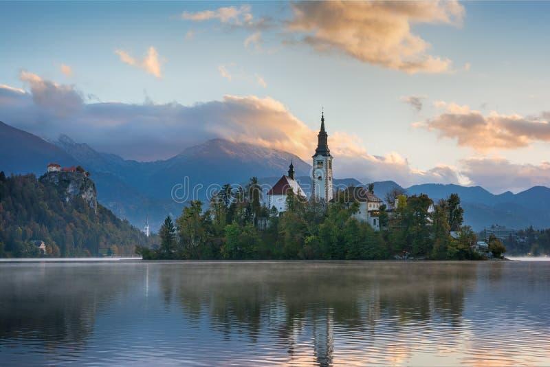 Το όμορφο τοπίο ανατολής της διάσημης λίμνης αιμορράγησε στη Σλοβενία με την εκκλησία στο μικρό πράσινο νησί στοκ φωτογραφίες