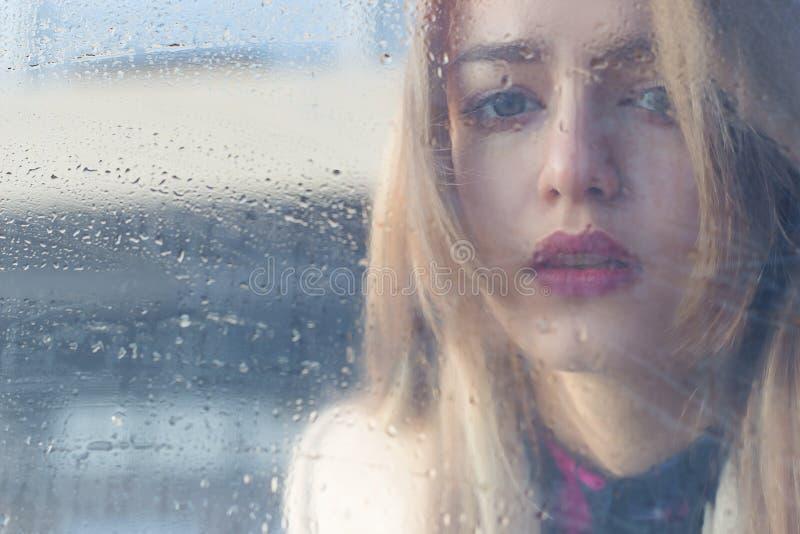 Το όμορφο λυπημένο κορίτσι με τα μεγάλα μάτια σε ένα παλτό είναι πίσω από το υγρό γυαλί στοκ φωτογραφία με δικαίωμα ελεύθερης χρήσης