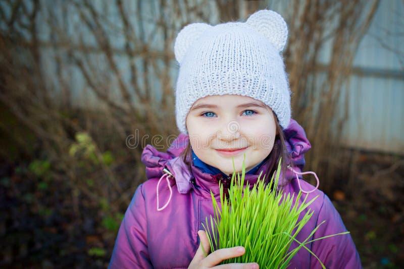 Το όμορφο χαμογελώντας κορίτσι με την πράσινη χλόη και εξετάζει τη κάμερα στοκ εικόνα με δικαίωμα ελεύθερης χρήσης