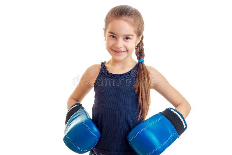 Το όμορφο χαμόγελο μικρών κοριτσιών που κοιτάζουν άμεσα και οι συντηρήσεις παραδίδουν τα εγκιβωτίζοντας γάντια είναι απομονωμένα  στοκ εικόνα