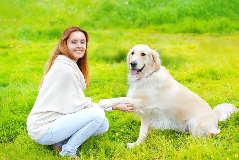 Το όμορφο χρυσό Retriever σκυλί δίνει τον ιδιοκτήτη ποδιών στη χλόη στοκ εικόνα με δικαίωμα ελεύθερης χρήσης
