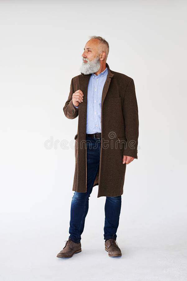 Το όμορφο ώριμο γενειοφόρο άτομο έντυσε στο παλτό φθινοπώρου στοκ εικόνες