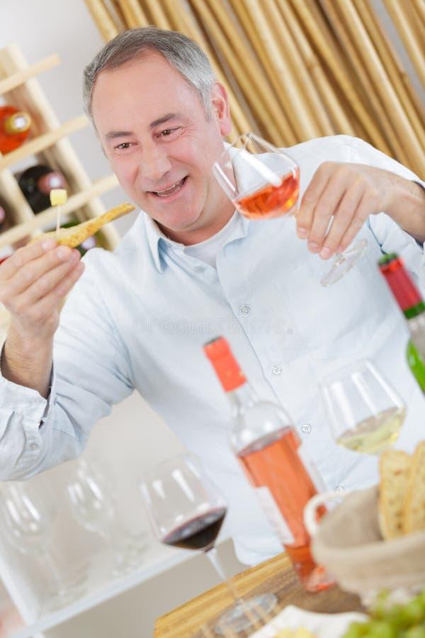 Το όμορφο ώριμο δοκιμάζοντας γυαλί ατόμων αυξήθηκε κρασί στοκ εικόνες