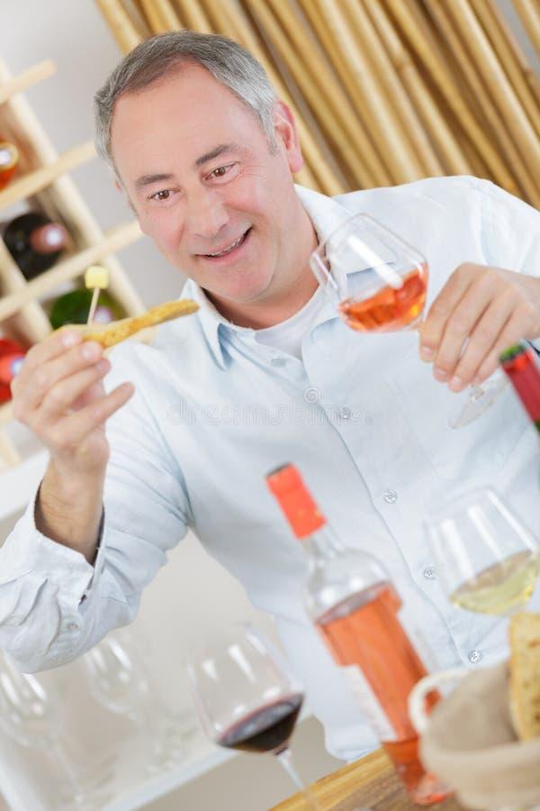 Το όμορφο ώριμο δοκιμάζοντας γυαλί ατόμων αυξήθηκε κρασί στοκ εικόνα με δικαίωμα ελεύθερης χρήσης