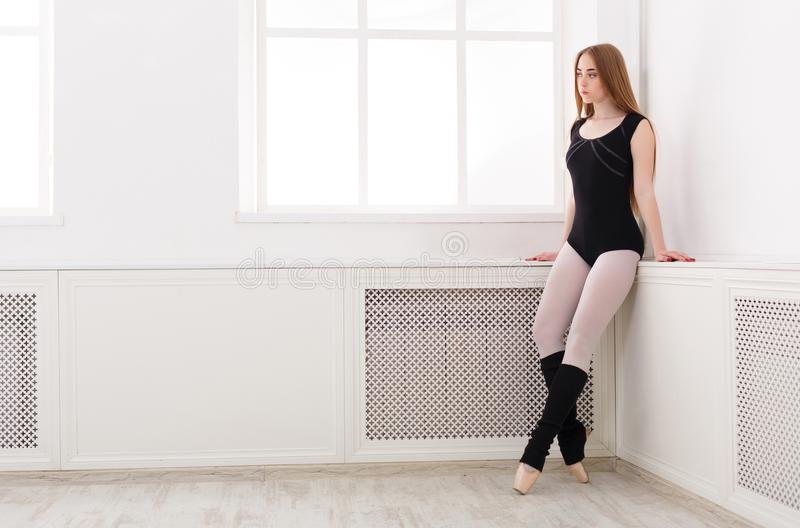 Το όμορφο ballerina στέκεται κοντά στο παράθυρο στοκ εικόνες
