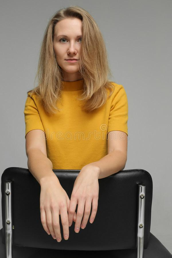 Το όμορφο blondie κάθεται στο στούντιο στοκ εικόνα