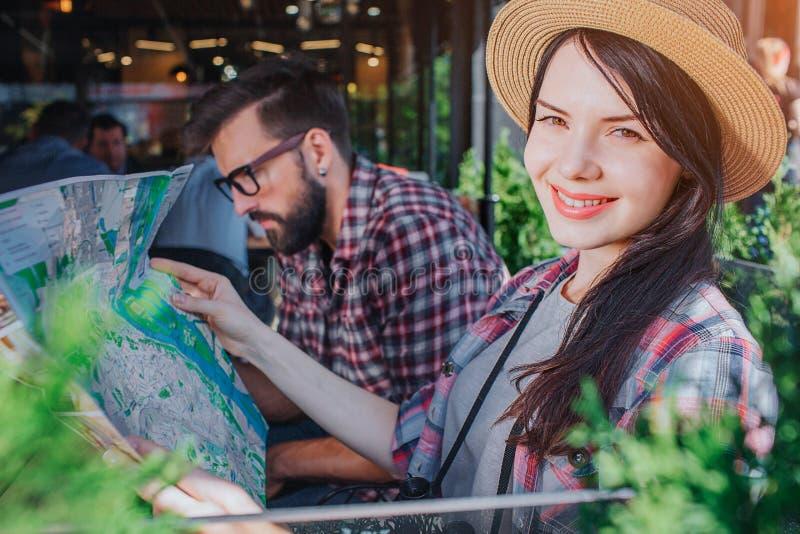 Το όμορφο brunette κάθεται και κοιτάζει στη κάμερα Χαμογελά και κρατά το χάρτη στα χέρια Ο νεαρός άνδρας κοιτάζει κάτω Είναι σοβα στοκ εικόνα