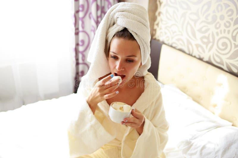 Το όμορφο brunette σε μια εσθήτα επιδέσμου και μια μπλούζα στο κεφάλι της έχει το πρόγευμα στο κρεβάτι στοκ φωτογραφία