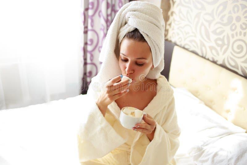 Το όμορφο brunette σε μια εσθήτα επιδέσμου και μια μπλούζα στο κεφάλι της έχει το πρόγευμα στο κρεβάτι στοκ εικόνες