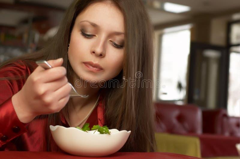 το όμορφο brunette τρώει τη σαλάτ&alph στοκ εικόνες