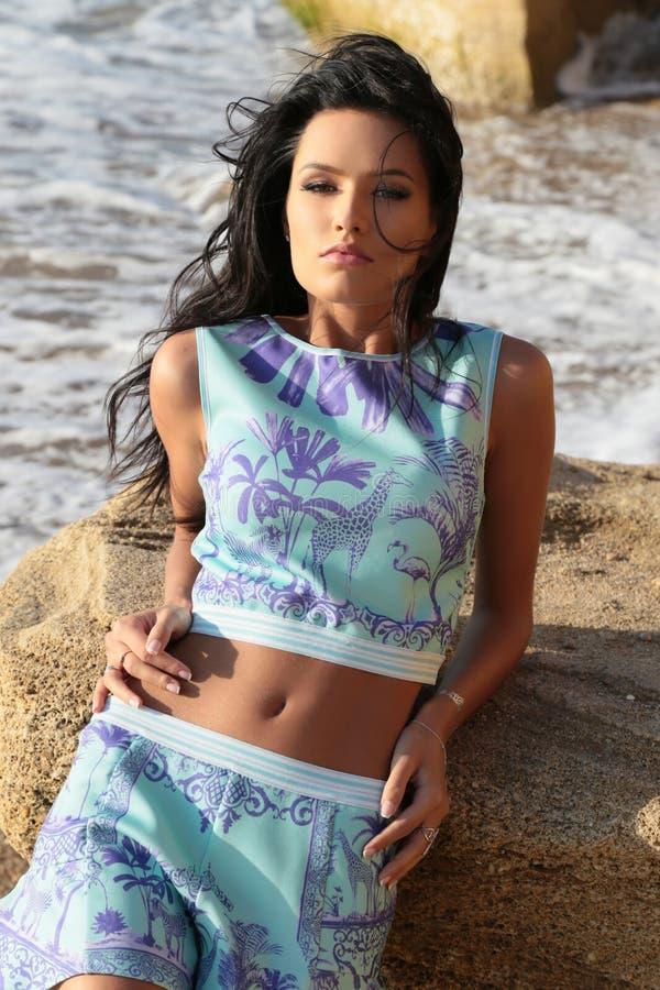 Download Το όμορφο Brunette φορά το κομψό φόρεμα με το κόσμημα, που θέτει στη θερινή παραλία Στοκ Εικόνα - εικόνα από κορίτσι, φόρεμα: 62700737