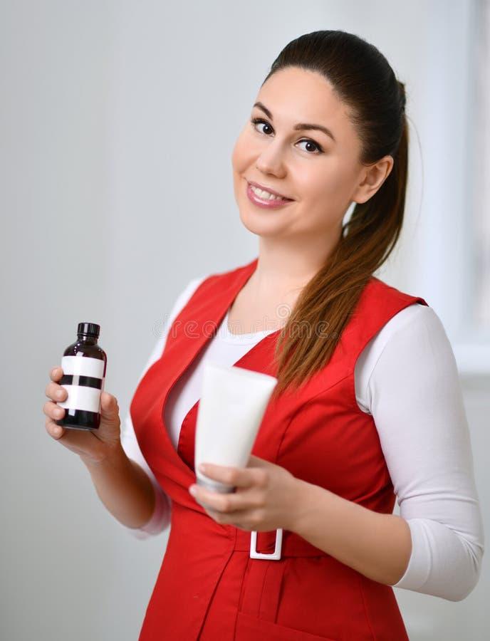 Το όμορφο cosmetician γιατρών στην ιατρική ομοιόμορφη κόκκινη ιατρική εσθήτα κρατά vian και σωλήνας με τα καλλυντικά στο άσπρο γρ στοκ εικόνα με δικαίωμα ελεύθερης χρήσης