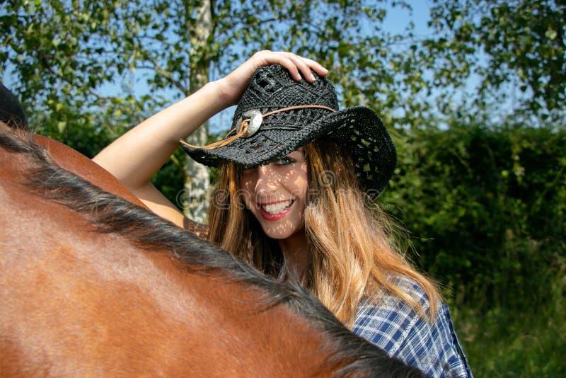 Το όμορφο cowgirl με το καπέλο και τα μπλε μάτια εξετάζουν τη κάμερα με το άλογο στο forground στοκ φωτογραφίες με δικαίωμα ελεύθερης χρήσης