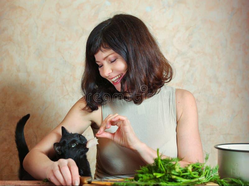 Το όμορφο houswife έκοψε το χαμόγελο γατών σίτισης κρέατος στοκ εικόνα με δικαίωμα ελεύθερης χρήσης