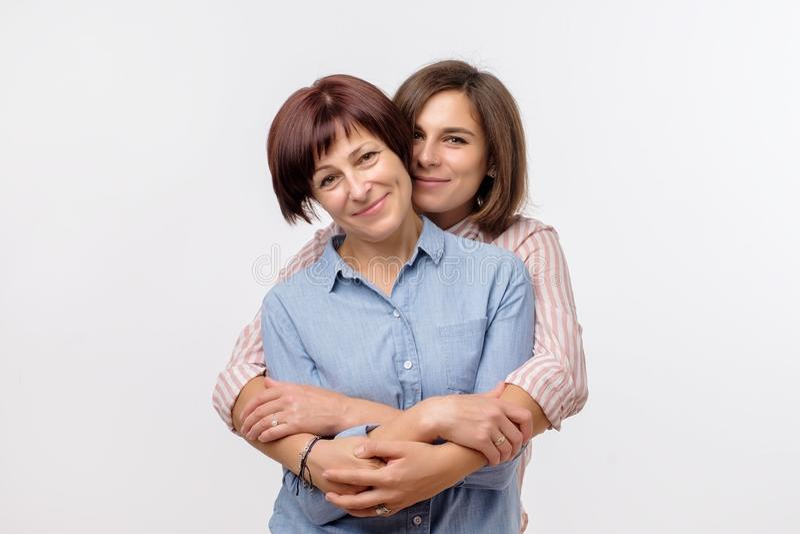 Το όμορφο maturesenior mom και η ενήλικη κόρη της αγκαλιάζουν, εξετάζουν τη κάμερα και χαμογελούν στοκ φωτογραφίες