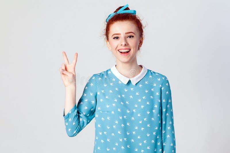 Το όμορφο redhead κορίτσι ευτυχίας παρουσιάζει σημάδι ειρήνης ή νίκης Απομονωμένο στούντιο που πυροβολείται στο γκρίζο υπόβαθρο στοκ εικόνα