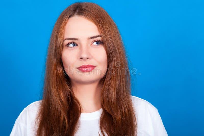 Το όμορφο redhead κορίτσι με τις φακίδες σε ένα μπλε υπόβαθρο σκέφτεται, πονηρό βλέμμα στοκ φωτογραφία με δικαίωμα ελεύθερης χρήσης