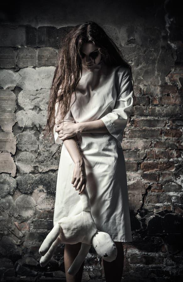 Το ύφος φρίκης πυροβόλησε: τρομακτικό κορίτσι τεράτων με την κούκλα moppet στα χέρια στοκ εικόνες