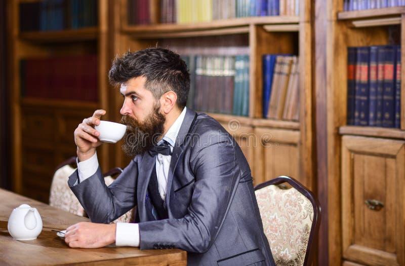 Το ώριμο άτομο με το ήρεμο πρόσωπο απολαμβάνει το τσάι απογεύματος στοκ εικόνες