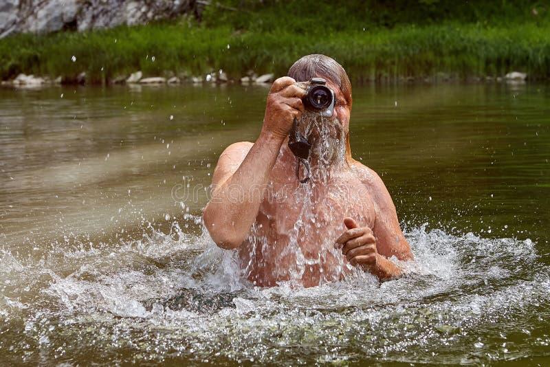 Το ώριμο άτομο χρησιμοποιεί την αδιάβροχη κάμερα στον ποταμό στοκ εικόνες