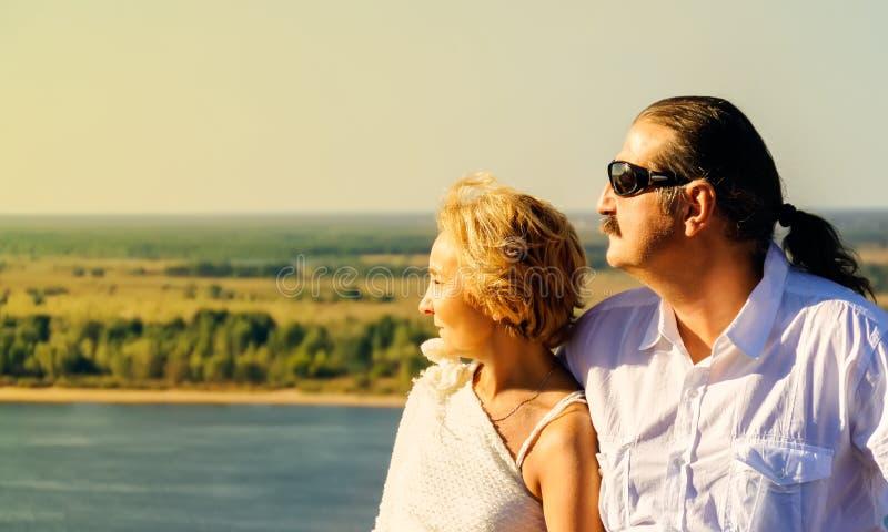 Το ώριμο ζευγάρι κοιτάζει μακρυά προς τον ερχόμενο ήλιο στοκ εικόνες