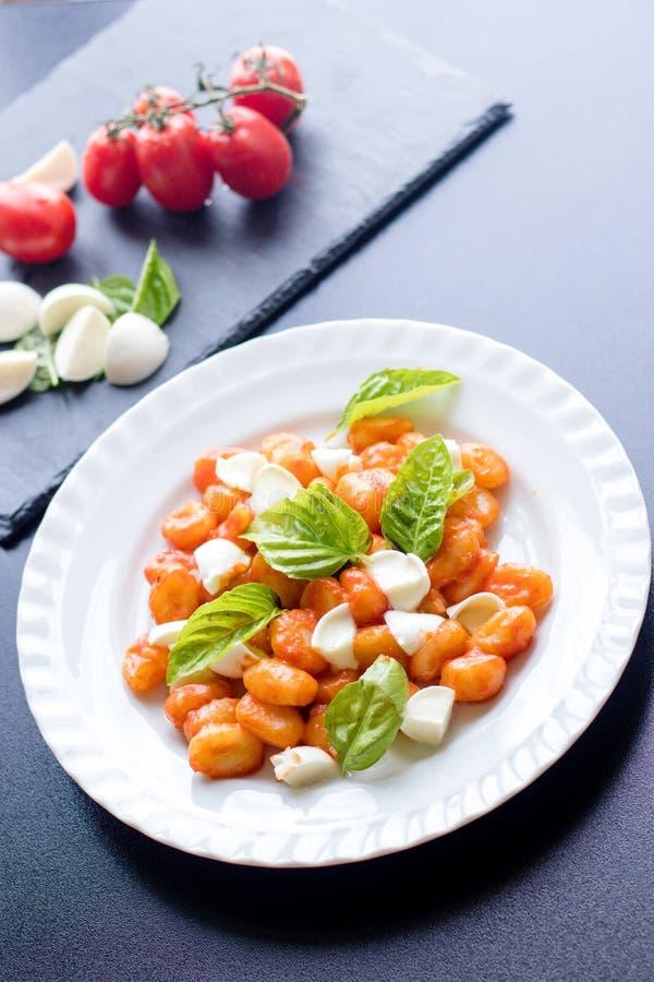 Το alla Sorrentina gnocchi πατατών στη σάλτσα ντοματών με τις πράσινες φρέσκες σφαίρες βασιλικού και μοτσαρελών εξυπηρέτησε σε έν στοκ εικόνα