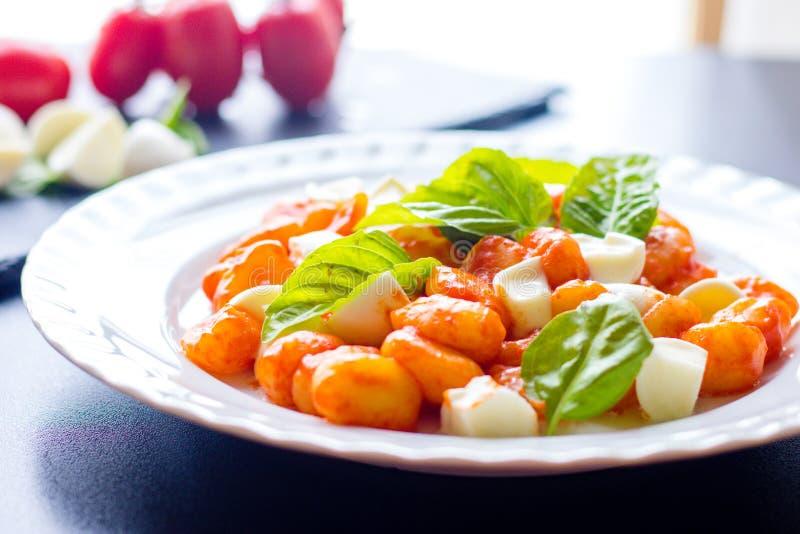 Το alla Sorrentina Gnocchi στη σάλτσα ντοματών με τις πράσινες φρέσκες σφαίρες βασιλικού και μοτσαρελών εξυπηρέτησε σε ένα πιάτο στοκ εικόνες με δικαίωμα ελεύθερης χρήσης