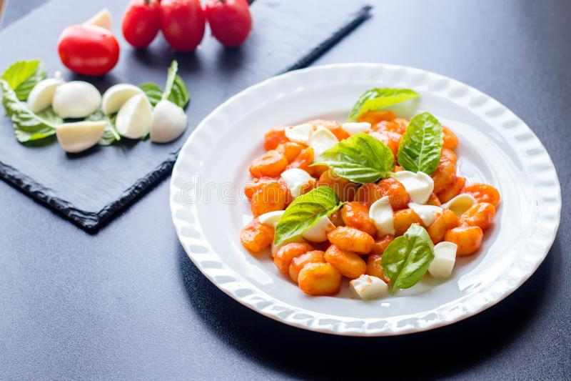Το alla Sorrentina Gnocchi στη σάλτσα ντοματών με τις πράσινες φρέσκες σφαίρες βασιλικού και μοτσαρελών εξυπηρέτησε σε ένα πιάτο στοκ φωτογραφίες με δικαίωμα ελεύθερης χρήσης
