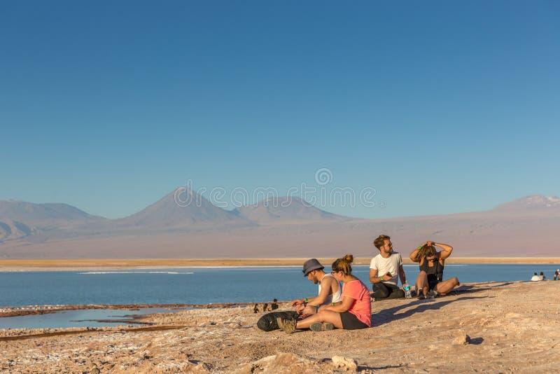 Το Atacama, Χιλή - 9 Οκτωβρίου 2017 - νέα ζεύγη που κάθονται μπροστά από το Atacama Salar, χαλαρώνοντας στιγμή, τα βουνά των Άνδε στοκ εικόνα