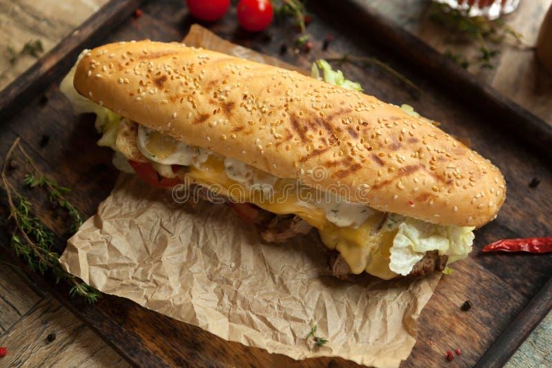 Το baguette σίτου, tenderloin βόειου κρέατος, έψησε το βασιλικό τυρί, ντομάτα, ι στη σχάρα στοκ φωτογραφία