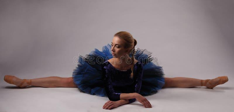 Το Ballerina στην μπλε εξάρτηση παρουσιάζει διάσπαση στο πάτωμα στούντιο στοκ φωτογραφία